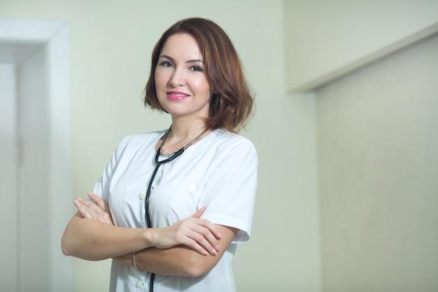 Aantrekkelijke vrouw in een witte jas bij de kliniek