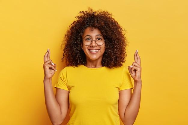 Aantrekkelijke vrouw in geel t shirt, kruist vingers, hoopt op een gelukkige toekomst, lacht aangenaam, vormt tegen een levendige achtergrond, bidt binnen