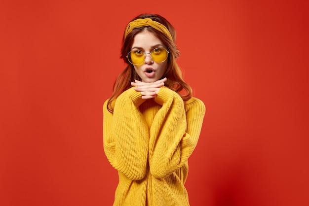 Aantrekkelijke vrouw in gele trui mode kapsel aantrekkelijk uiterlijk rode muur.