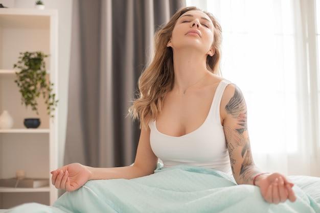 Aantrekkelijke vrouw in haar pyjama wakker. positieve vrouw in de ochtend.