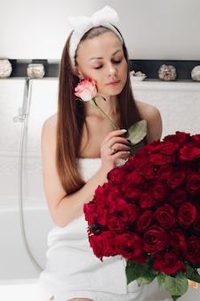 Aantrekkelijke vrouw in handdoek en hoofdband met boeket van rode rozen