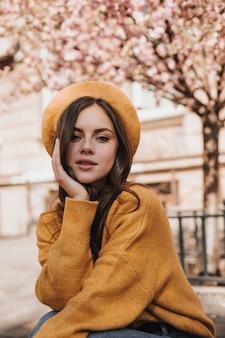 Aantrekkelijke vrouw in heldere baret en trui kijkt naar de camera tegen de achtergrond van het gebouw. mooie jonge brunette dame in goed humeur poseren in stad tegen sakura