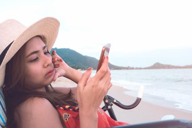 Aantrekkelijke vrouw in hoed die smartphone gebruiken terwijl het zitten op ligstoel bij zonsondergangstrand.