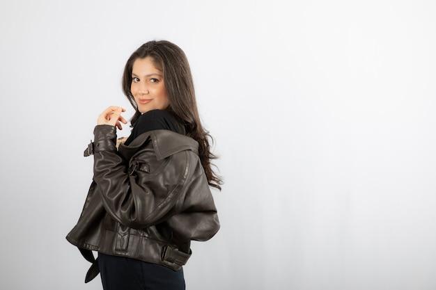 Aantrekkelijke vrouw in jas staan en poseren.