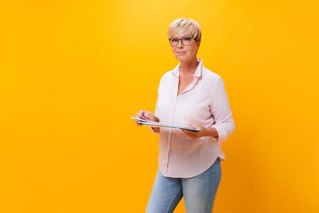 Aantrekkelijke vrouw in jeans en roze shirt vormt met documenten op oranje achtergrond