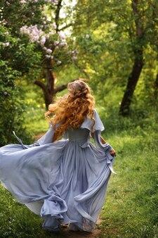 Aantrekkelijke vrouw in jurk en met kapsel loopt door de zomertuin