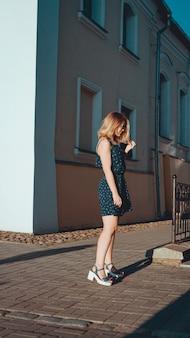 Aantrekkelijke vrouw in jurk loopt op een zonnige dag door de straten van de oude stad. verticale foto