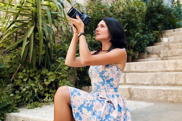 Aantrekkelijke vrouw in jurk treveling op vakantie in europa aan zee op een cruise die foto's maakt op de camera