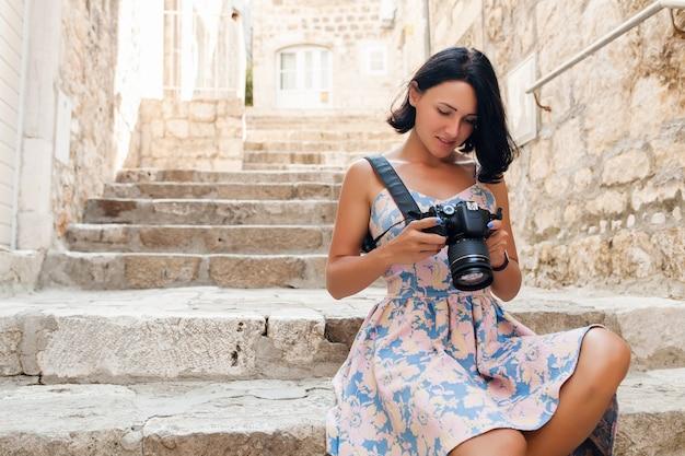 Aantrekkelijke vrouw in jurk treveling op vakantie in het oude centrum van italië, fotograferen op de camera