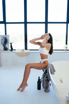 Aantrekkelijke vrouw in lingerie poseren in de buurt van het bad. meisje poseert voor de camera