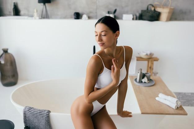 Aantrekkelijke vrouw in lingerie poseren in de buurt van het bad