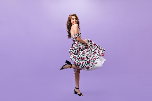 Aantrekkelijke vrouw in midi jurk dansen op paarse achtergrond. prachtig krullend meisje in bloemenkleren en zwarte schoenen glimlachen.