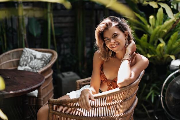 Aantrekkelijke vrouw in oranje beha en witte korte broek glimlacht wijd