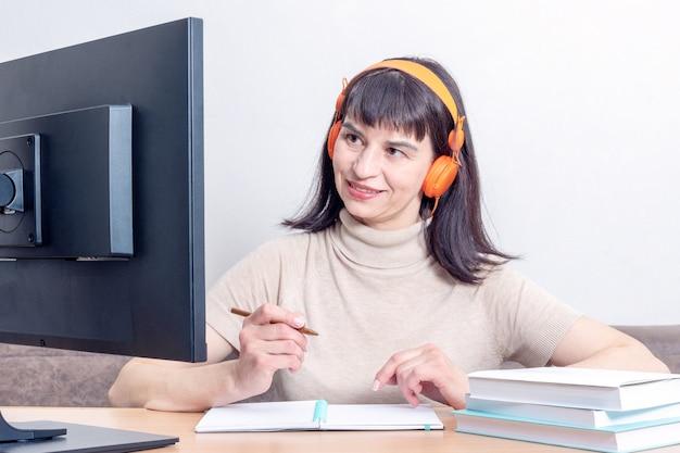 Aantrekkelijke vrouw in oranje koptelefoon zittend aan een tafel met boeken, kijken naar een computermonitor, met een pen boven een notebook