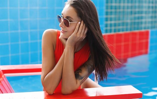 Aantrekkelijke vrouw in rode bikini en zonnebril, die opzij kijkt.