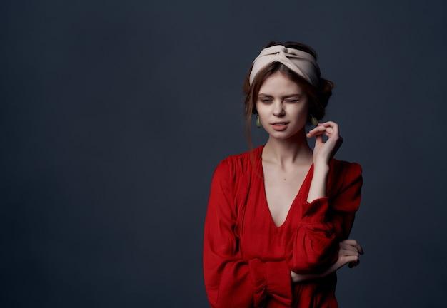 Aantrekkelijke vrouw in rode jurk luxe feest donkere achtergrond