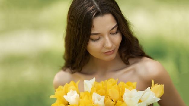 Aantrekkelijke vrouw in rode jurk met een boeket van lentebloemen tegen natuur bokeh groen