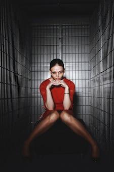 Aantrekkelijke vrouw in rode jurk poseren in een kooi