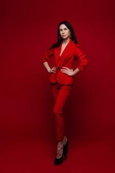 Aantrekkelijke vrouw in rood pak en zwarte hakken
