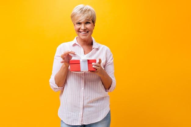 Aantrekkelijke vrouw in roze outfit poseren met geschenkdoos op oranje achtergrond