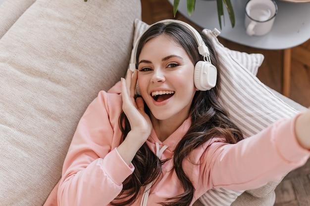Aantrekkelijke vrouw in roze sweatshirt ligt op de bank, genietend van muziek in de koptelefoon en maakt selfie