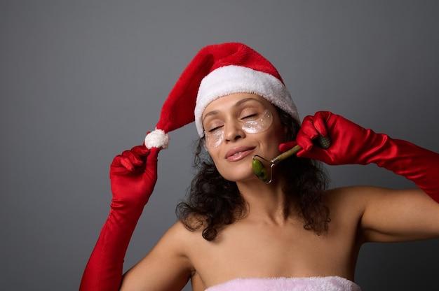 Aantrekkelijke vrouw in santa kostuum gebruikt jade roller stimulator voor facelift en lymfedrainage gezichtsmassage. huidverzorging, cosmetologieconcept voor kerstadvertentie van schoonheidssalons en spa