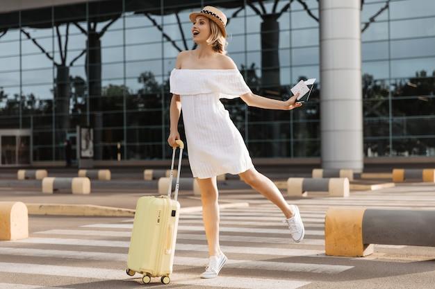 Aantrekkelijke vrouw in schipper en witte jurk springt in de buurt van luchthaven