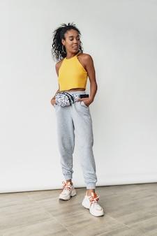 Aantrekkelijke vrouw in stijlvolle hipster outfit gele top op witte geïsoleerde muur