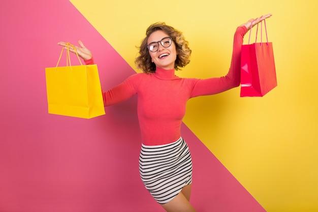Aantrekkelijke vrouw in stijlvolle kleurrijke outfit met boodschappentassen verlaten