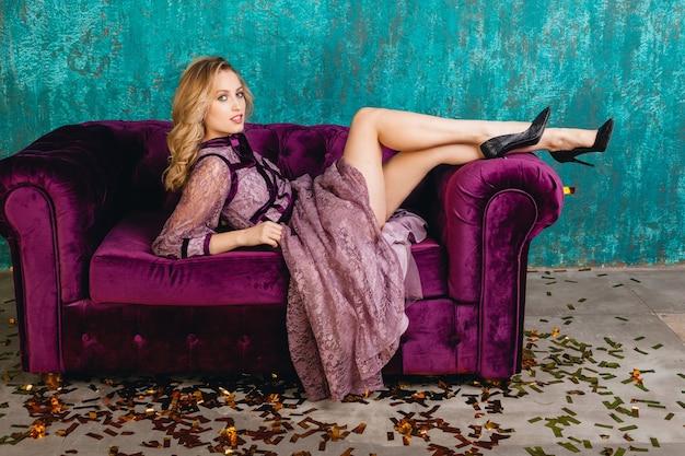 Aantrekkelijke vrouw in stijlvolle violet kant avondjurk liggend op fluwelen sofa