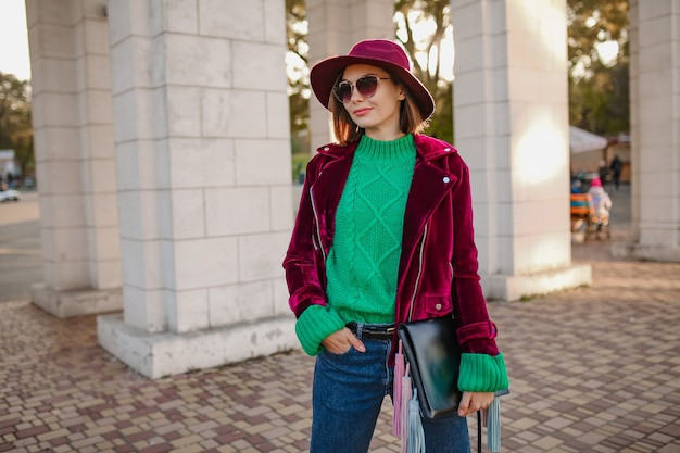 Aantrekkelijke vrouw in trendy herfstoutfit die op straat loopt met een paars fluwelen jasje, zonnebril en hoed, groene gebreide trui, handtas vast