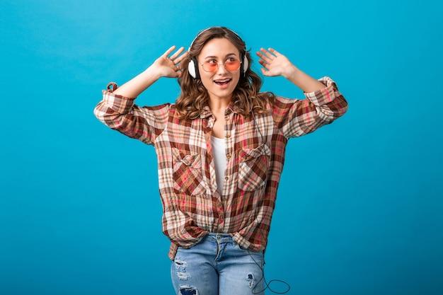 Aantrekkelijke vrouw in vrolijke opgewonden stemming en blij gezicht expressie luisteren naar muziek in koptelefoon in geruit overhemd en spijkerbroek geïsoleerd op blauwe studio achtergrond