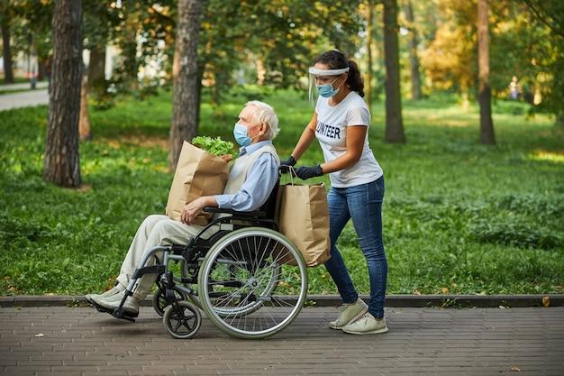 Aantrekkelijke vrouw in wit overhemd en spijkerbroek die van mooi weer geniet met volwassen gehandicapte man