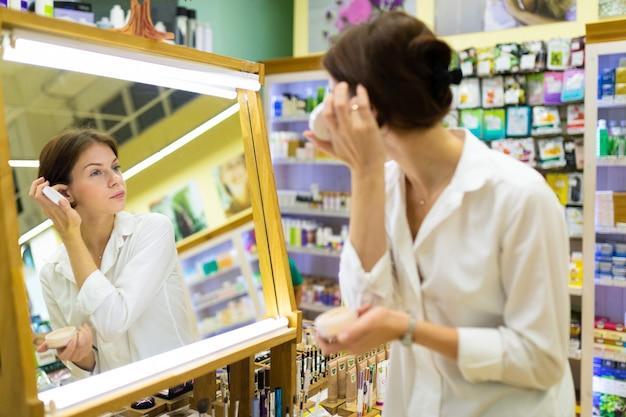 Aantrekkelijke vrouw in wit overhemd kijkt naar haar spiegelbeeld