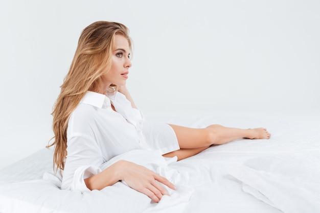 Aantrekkelijke vrouw in wit overhemd liggend in bed en wegkijkend