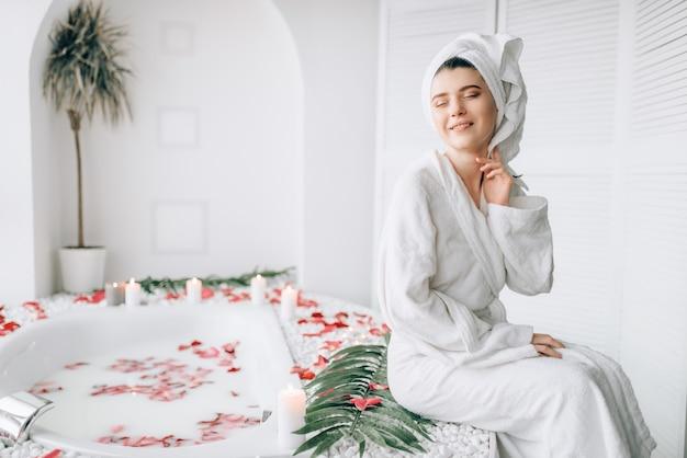 Aantrekkelijke vrouw in witte badjas en handdoek op hoofd zittend op de rand van het bad versierd met rozenblaadjes.