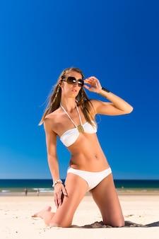 Aantrekkelijke vrouw in witte bikinizitting in de zon op strand, heel wat copyspace in de blauwe hemel