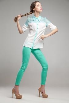 Aantrekkelijke vrouw in witte blouse en turquoise broek poseren in studio