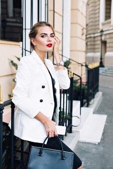 Aantrekkelijke vrouw in witte jas leunt op hek op straat. ze kijkt naar de camera.