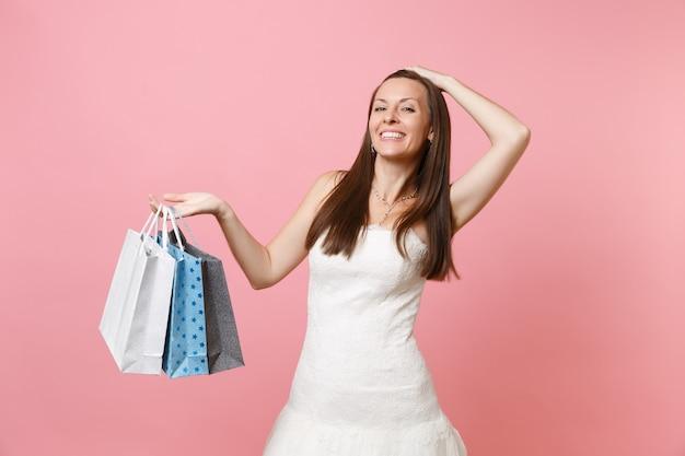 Aantrekkelijke vrouw in witte jurk die de hand op het hoofd houdt en na het winkelen veelkleurige pakketten met aankopen vasthoudt