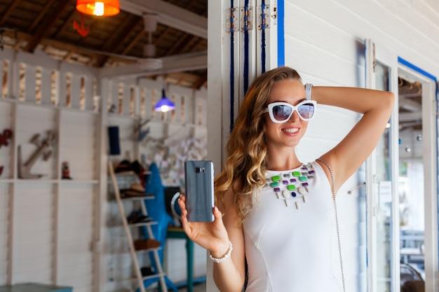 Aantrekkelijke vrouw in witte jurk in zomerterras in zonnebril met behulp van telefoon foto nemen