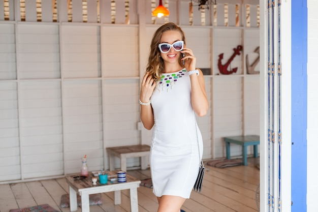 Aantrekkelijke vrouw in witte jurk in zomerterras in zonnebril praten over de telefoon