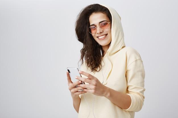 Aantrekkelijke vrouw in zonnebril met behulp van smartphone en glimlachen
