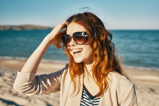 Aantrekkelijke vrouw in zonnebril op het zand in de buurt van de zee in de bergen