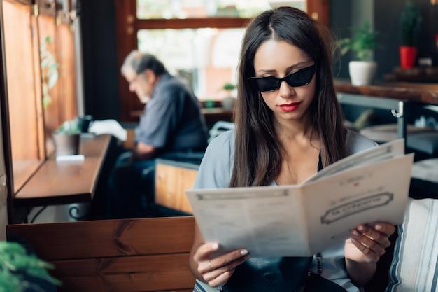 Aantrekkelijke vrouw in zonnebril zit in een restaurant.