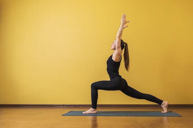 Aantrekkelijke vrouw in zwarte sportkleding het beoefenen van yoga voert virabhadrasana-oefening warrior pose 1 uit tegen een gele muur
