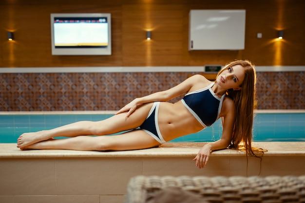 Aantrekkelijke vrouw in zwembroek liggend bij het zwembad binnenshuis.