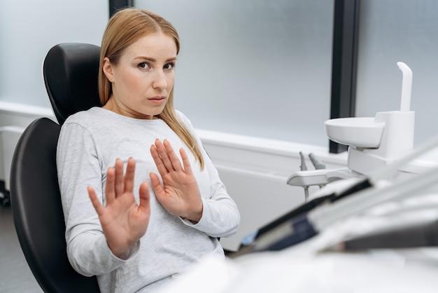 Aantrekkelijke vrouw is bang om tanden te behandelen. een vrouw in de tandartspraktijk toont een gebaar zodat niemand komt