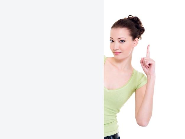 Aantrekkelijke vrouw kijkt uit van lege banner met wijsvinger omhoog. idee concept
