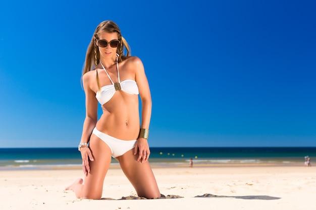 Aantrekkelijke vrouw knielt in de zon op het strand